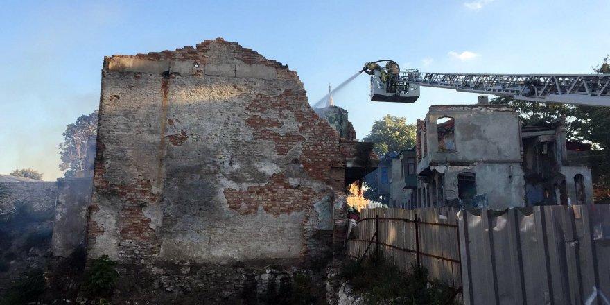 Yanan metruk binanın duvarı aracın üzerine çöktü