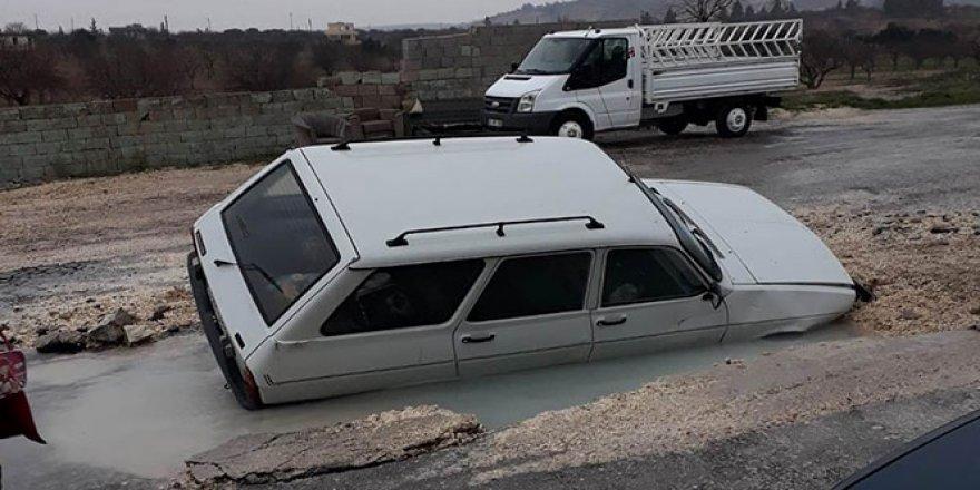 Otomobil yolda oluşan dev çukura düştü
