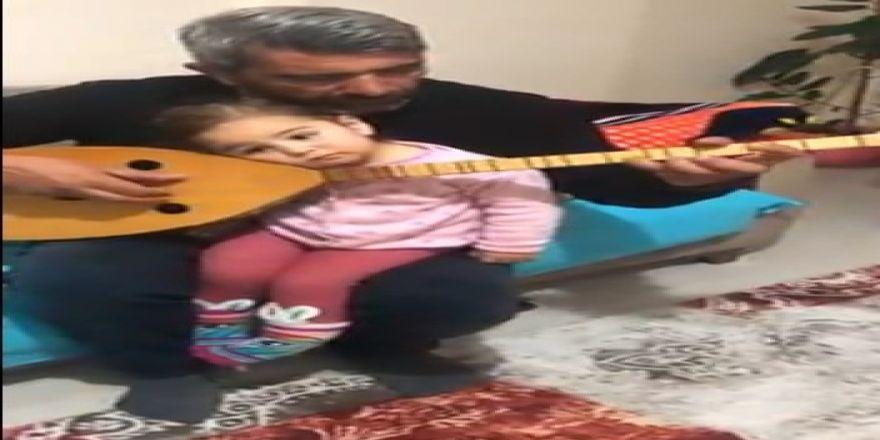 Küçük kızını bağlama ve türküyle uyutuyor