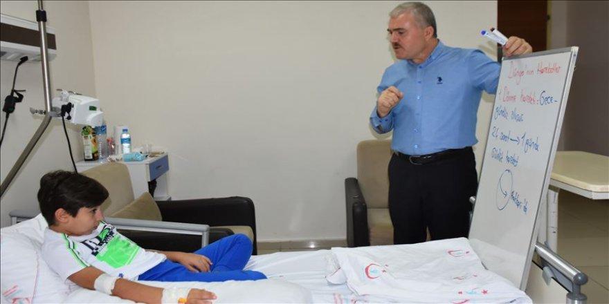 Öğrencisine hastane odasında ders veriyor