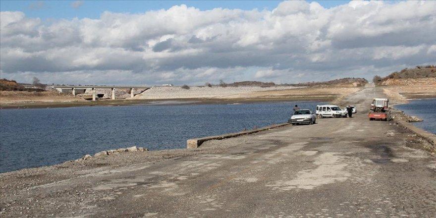 Barajdaki su seviyeyi düşünce ortaya çıkan eski yoldan olta atıp balık avlıyorlar