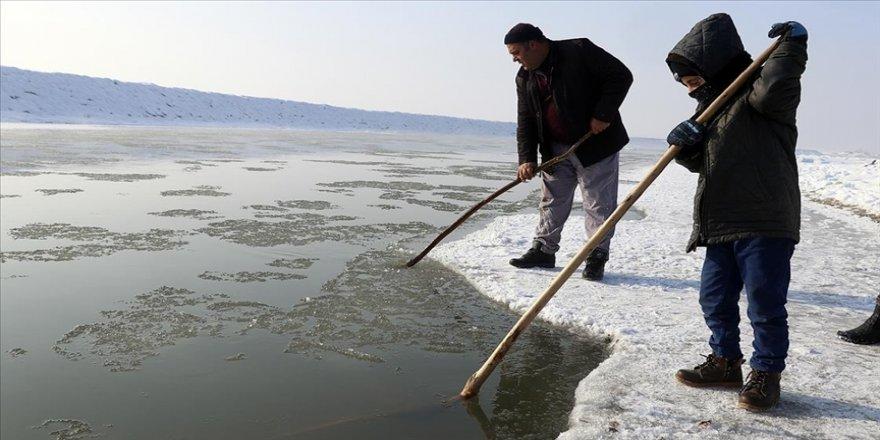Ekmek parası için dondurucu soğuğa rağmen nehirdeki buzları kırıp balık avlıyorlar
