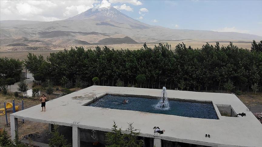 Bahçe işlerinden fırsat bulup tatile götürmediği çocukları için Ağrı Dağı manzaralı havuz inşa etti