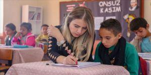 Elif öğretmen okuma yazma öğrettiği çocuklar ve anneleriyle kitap okuyor