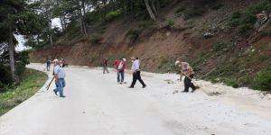 Yeni yapılan köy yolunu zarar görmesin diye kürek ve süpürgeyle temizliyorlar