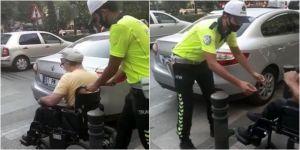 Geçide park edilen otomobil nedeniyle karşıya geçemeyen engellinin yardımına polis koştu