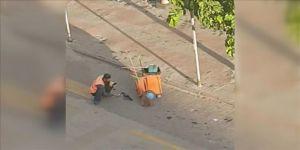 Temizlik görevlisinin yol kenarındaki kargayı elleriyle beslediği anlar kamerada