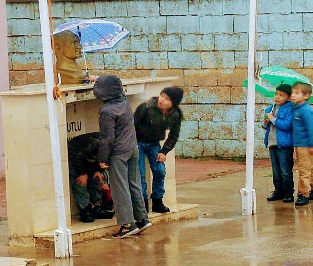 Minik öğrenciler Atatürk büstü ıslanmasın diye şemsiye tuttular